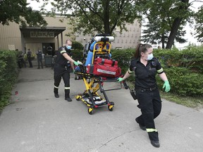 Paramedics transport a woman from the River Place apartments for unknown reasons on Wednesday, July 21, 2021. Several individuals were evicted from the building after the city deemed it unsafe.