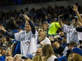 Toronto Blue Jays fans interact with the Blue Jays mascot during a break in the action against the New York Yankees at the Rogers Centre in Toronto, Ont. on Thursday, March 29, 2018.