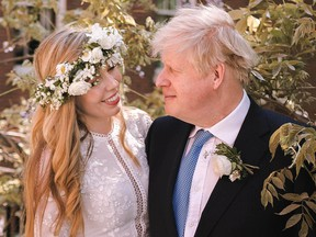 Boris Johnson poses with his wife Carrie Johnson in the garden of 10 Downing Street following their wedding at Westminster Cathedral, May 29, 2021 in London.