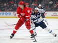 Tyler Bertuzzi of the Detroit Red Wings look to pass the puck in front of Mathieu Perreault of the Winnipeg Jets at Little Caesars Arena on December 12, 2019 in Detroit.