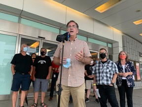 Windsor West MP Brian Masse speaks at an entrance to Caesars Windsor with members of Unifor Local 444 behind him on Aug. 27, 2021.