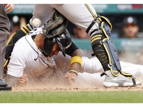 Detroit Tigers second baseman Harold Castro slides in safe at home ahead of the tag by Milwaukee Brewers catcher Manny Pina in the fifth inning at Comerica Park.