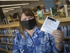 Sue Perry, team leader at the Windsor Public Library, holds a recently laminated vaccine passport at the downtown branch, a service the Windsor Public Library is providing free of charge, on Tuesday, Sept. 28, 2021.