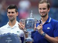 Novak Djokovic of Serbia and Daniil Medvedev of Russia celebrate with the finalist and championship trophies, respectively, after their match in the men's singles final on day fourteen of the 2021 U.S. Open tennis tournament at USTA Billie Jean King National Tennis Center.