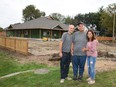 The Piunno family, Ernie, Christian and Susana stand in front of the nearly completed Family Respite Home on Howard Ave.