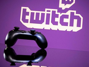 In this file photo taken on June 15, 2021, a gamepad is pictured as a screen displays the online Twitch plateform in Toulouse, southwestern France.