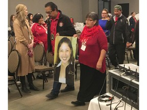 Bernice Catcheway, right, carries a picture of her daughter, Jennifer Catcheway, into a hearing of the national inquiry into missing and murdered women in Winnipeg on Friday Oct. 20, 2017. Jennifer Catcheway disappeared in 2008 and her family says they feel abandoned by police and other authorities as they continue to search for her. THE CANADIAN PRESS/Steve Lambert ORG XMIT: CPT111 Steve Lambert,