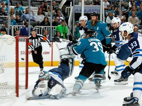 Logan Couture (39) of the San Jose Sharks get the puck by Winnipeg Jets goalie Steve Mason to score a first period goal in San Jose on Saturday. Mason left Saturday's game after the first period with an upper-body injury after taking a slapper off the mask.