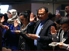 People take the citizenship oath during a special citizenship ceremony at the Canadian Museum of Human Rights in Winnipeg on Sun., Dec. 10, 2017. Kevin King/Winnipeg Sun/Postmedia Network