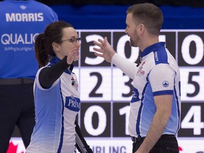 Val Sweeting and Brad Gushue congratulate each other after defeating John Morris and Kaitlyn Lawes to gain a berth in Sunday's final of the trials.