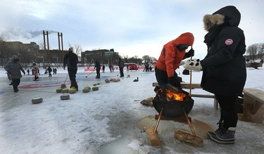 People warm up by the fire during the 17th annual Ironman Outdoor Curling Bonspiel on the Red River at The Forks in Winnipeg on Sun., Feb. 4, 2018. Kevin King/Winnipeg Sun/Postmedia Network