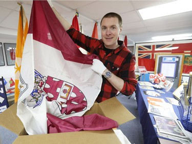 Shayne Campbell, who is the president and executive director of Settlers, Rails & Trails, holds out a McMaster University flag from the Ralph Spence collection which arrived at the local museum in Argyle, Man., located 50 kilometres northwest of Winnipeg, Man. on Friday, March 2, 2018. (Brook Jones/Stonewall Argus & Teulon Times/Postmedia Network)