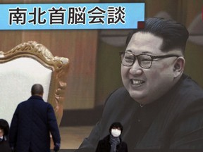 """People walk past a public TV screen showing North Korean leader Kim Jong Un, in Tokyo Wednesday, March 7, 2018. After years of refusal, North Korean leader Kim Jong Un is willing to discuss the fate of his atomic arsenal with the United States and has expressed a readiness to suspend nuclear and missile tests during such talks, a senior South Korean official said Tuesday. Japanese characters read: """"North-South summit talks."""""""