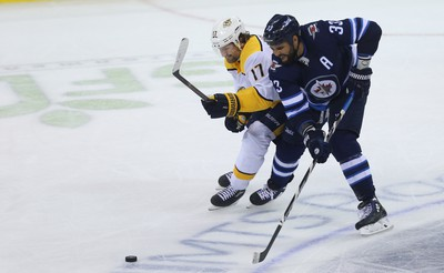 Winnipeg Jets defenceman Dustin Byfuglien (right) battles for the puck with Nashville Predators forward Scott Hartnell during Game 4 of their second-round NHL playoff series in Winnipeg on Thurs., May 3, 2018. Kevin King/Winnipeg Sun/Postmedia Network