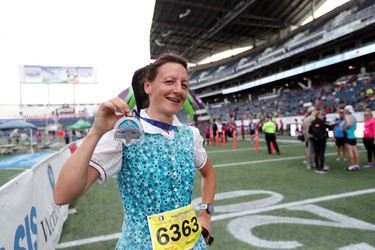 Tracey Hofer of Westbourne, Man., shows off her finisher medal after competing in the half marathon at the 40th annual Manitoba Marathon in Winnipeg, Man., on Sunday, June 17, 2018. (Brook Jones/Postmedia Network)