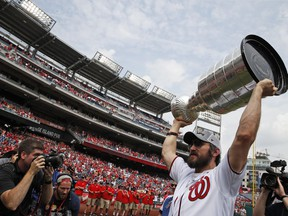 Washington Capitals' Alex Ovechkin, from Russia, lifts the Stanley Cup on the field before a baseball game between the Washington Nationals and the San Francisco Giants at Nationals Park, Saturday, June 9, 2018, in Washington.