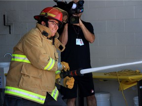 Isaiah Hunt, a camper from the Winnipeg Fire Paramedic Services (WFPS) career camp, shoots a fire hose during a firefighter and paramedic relay course during the final day of the week long camp at the WFPS Training Academy on Friday.