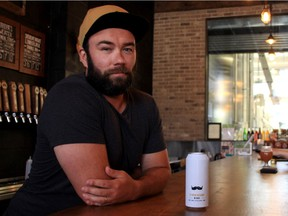 Tyler Birch, owner of Barn Hammer Brewing, sits at his bar in Winnipeg with a can of Barn Hammer brewed beer, a product that has recently become more expensive to produce because of the 10% tariff on aluminum products from the United States.