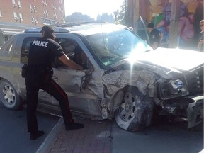 A Winnipeg Police Service officer examines a stolen Cadillac Escalade whose driver led police on a wild chase Friday at around 10:15 a.m., on Furby Street between Sargent Avenue and Ellice Avenue, reaching speeds of over 100 km/h on the sidewalk and damaging several fences and colliding with a business before crashing head-on into an apartment building.