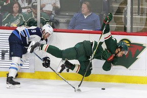 Jets' Andrew Copp (left) upends Wild centre Jordan Greenway during the second period in St. Paul, Minn., last night. AP
