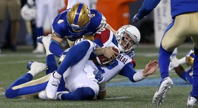 Montreal Alouettes QB Johnny Manziel is stopped on a run by Winnipeg Blue Bombers LB Adam Bighill (top) and Jovan Santos-Knox (bottom) Friday at Investors Group Field. (Kevin King/Winnipeg Sun)