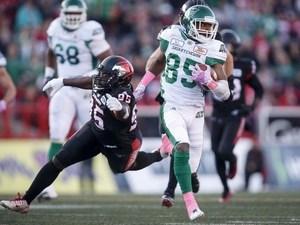 Saskatchewan Roughriders' Kyran Moore, right, escapes the grasp of Calgary Stampeders' Ja'Gared Davis during CFL football action in Calgary, Saturday, Oct. 20, 2018. THE CANADIAN PRESS/Jeff McIntosh ORG XMIT: JMC106