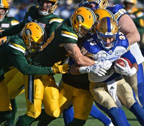 A team of Edmonton Eskimos wrap up Winnipeg Blue Bombers running back Andrew Harris (33) during CFL action in the last game of the season at Commonwealth Stadium in Edmonton, November 3, 2018. (Ed Kaiser/Postmedia Network)