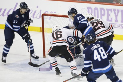 Chicago Blackhawks' Marcus Kruger (16) scores on Winnipeg Jets goaltender Connor Hellebuyck (37) during first period NHL action in Winnipeg on Thursday, November 29, 2018. THE CANADIAN PRESS/John Woods