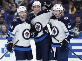 Winnipeg Jets' Patrik Laine, of Finland, is congratulated by Josh Morrissey (44) and Kyle Connor (81) after scoring during the first period of an NHL hockey game against the St. Louis Blues, Saturday, Nov. 24, 2018, in St. Louis.