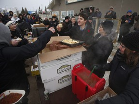 Prime Minister Justin Trudeau enjoys some bannock at a street party after announcing to the residents the opening of the repaired railway in Churchill, Manitoba Thursday, November 1, 2018. Prime Minister Justin Trudeau visited Churchill today to announce the opening of the railway and the Port of Churchill. THE CANADIAN PRESS/John Woods
