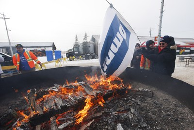 Patricia Kandiurin burns an OmniTrax banner at a street party celebrating the opening of the repaired railway in Churchill, Manitoba Thursday, November 1, 2018. Prime Minister Justin Trudeau visited Churchill today to announce the opening of the railway and the Port of Churchill. THE CANADIAN PRESS/John Woods