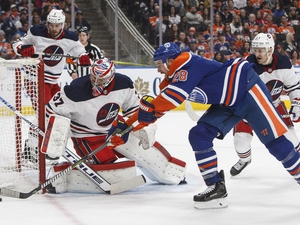 Winnipeg Jets' goalie Connor Hellebuyck (37) makes the save on Edmonton Oilers' Kyle Brodziak (28) during second period NHL action in Edmonton on Monday, Dec. 31, 2018. THE CANADIAN PRESS/Jason Franson