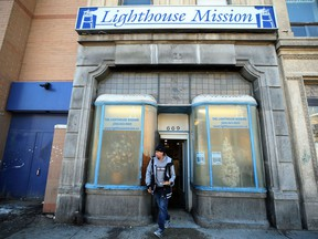 A man carries his pizza lunch out of the Lighthouse Mission soup kitchen on Main Street in Winnipeg on Sun., Dec. 9, 2018. Kevin King/Winnipeg Sun/Postmedia Network