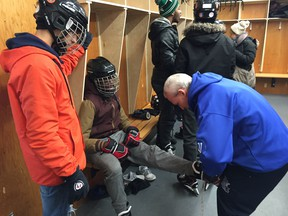 """Camp Manitou Director Rick Bochinski tightens the skates of one of the Congo Canada Charity Foundation participants in the True North Youth Foundation (TNYF) last of six 2018-19 """"Welcome to Winnipeg"""" events at Camp Manitou near Headingley on Saturday."""