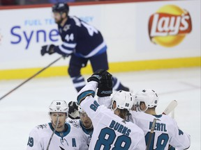 San Jose Sharks' Logan Couture (39) celebrates with his line after scoring as Winnipeg Jets' Josh Morrissey (44) skates off the ice during first period on Tuesday night. Josh Morrissey had been hurt prior to the goal. THE CANADIAN PRESS/Trevor Hagan