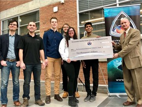 Wayne Ellis of the Canadian Satellite Design Challenge (far right) presents the cheque to Sanjay Abraham (second from right) and other members of the University of Manitoba Space Applications and Technology Society (UMSATS) team on Monday.