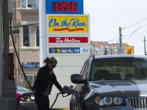 A woman pumps gas in Toronto on Tuesday, May 10, 2011. People in Manitoba, Ontario, Saskatchewan and New Brunswick will be paying more for gasoline and heating fuel Monday when the federal government's carbon tax begins in provinces that refused to impose their own emissions pricing.Nathan Denette / THE CANADIAN PRESS