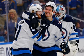 Jets' Kyle Connor is congratulated by Jack Roslovic after scoring the game-winning goal in overtime against the St. Louis Blues in Game Four of the Western Conference first round in St. Louis on Tuesday night. (Photo by Dilip Vishwanat/Getty Images)