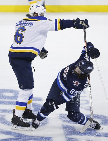 Winnipeg Jets' Mathieu Perreault (85) gets checked by St. Louis Blues' Joel Edmundson (6) during third period NHL playoff action in Winnipeg on Wednesday, April 10, 2019. THE CANADIAN PRESS/John Woods