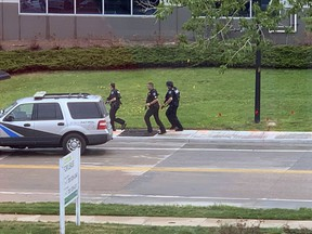 Armed police officers and others are seen outside STEM School Highlands Ranch, a charter middle school in the Denver suburb of Highlands Ranch, Colo., after a shooting Tuesday, May 7, 2019. Authorities said several people were injured and a few suspects were in custody.