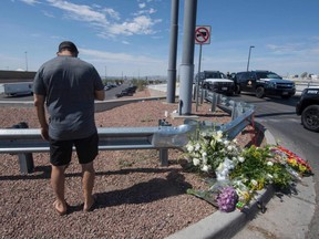 Alfredo Angcana prays beside a makeshift memorial outside the Cielo Vista Mall Wal-Mart where a shooting left 20 people dead in El Paso, Texas, on Sunday, Aug. 4, 2019.
