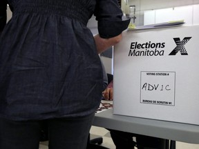 A woman prepares to cast an advance vote at the returning office at Corydon Community Centre's Crescentwood site on Corydon Avenue in Winnipeg on Wed., Sept. 4, 2019. Kevin King/Winnipeg Sun/Postmedia Network
