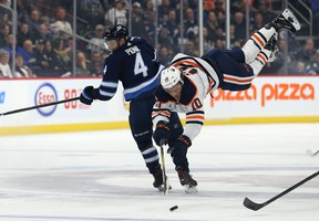 Jets defenceman Neal Pionk (left) upends Oilers forward Joakim Nygard with a hip at Bell MTS Place last night. Kevin King/Winnipeg Sun