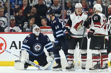 Winnipeg Jets goaltender Connor Hellebuyck (left) looks up at Josh Morrissey after a clearing attempt went into the Jets net during NHL action against the Phoenix Coyotes in Winnipeg on Tues., Oct. 15, 2019. Christian Dvorak (18) was credited with the goal. Kevin King/Winnipeg Sun/Postmedia Network