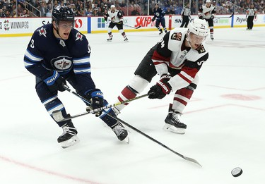 Winnipeg Jets centre Andrew Copp (left) and Phoenix Coyotes centre Carl Soderberg whack at a loose puck during NHL action in Winnipeg on Tues., Oct. 15, 2019. Kevin King/Winnipeg Sun/Postmedia Network