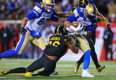 Andrew Harris of the Winnipeg Blue Bombers avoids a tackle from Hamilton Tiger-Cats Cariel Brooks during the 107th Grey Cup CFL championship football game in Calgary on Sunday, November 24, 2019. Al Charest/Postmedia