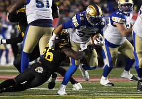 Winnipeg Blue Bombers running back Andrew Harris (33) runs the ball against Hamilton Tiger-Cats defensive back Cariel Brooks (26) in the second half during the 107th Grey Cup championship football game at McMahon Stadium in Calgary on Nov 24, 2019.