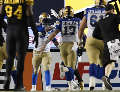 Nov 24, 2019; Calgary, Alberta, CAN; Winnipeg Blue Bombers running back Andrew Harris (33) celebrates with quarterback Chris Streveler (17) after scoring a touchdown against the Hamilton Tiger-Cats in the first half during the 107th Grey Cup championship football game at McMahon Stadium. Mandatory Credit: Eric Bolte-USA TODAY Sports