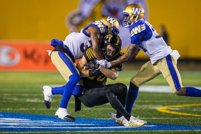 Nov 24, 2019; Calgary, Alberta, CAN; Hamilton Tiger-Cats wide receiver Jaelon Acklin (80) is tackled by Winnipeg Blue Bombers in the second half during the 107th Grey Cup championship football game at McMahon Stadium. Mandatory Credit: Sergei Belski-USA TODAY Sports