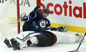 Jets' Mark Scheifele (left) pleads his innocence after barrelling into Colorado Avalanche goaltender Pavel Francouz during the opening minute of Tuesday night's game in Winnipeg. Francouz left the game injured.(KEVIN KING/WINNIPEG SUN)